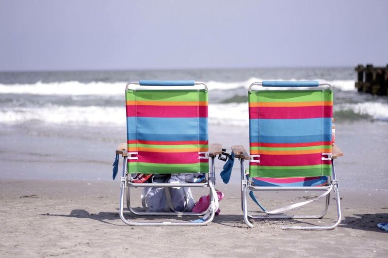 Colorful folding chairs on shore at beach against sky