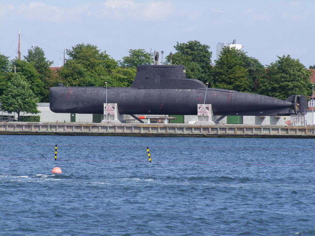 Old Submarine viewed from Larsens Plads Boat Cloudy Sky Composition Copenhagen Denmark History Mode Of Transport Navy No People Non-urban Scene Old On Display Out Of Service Outdoor Photography Ripples In The Water Sea Submarine Tourism Tourist Attraction  Tourist Destination Tree Water Waterfront