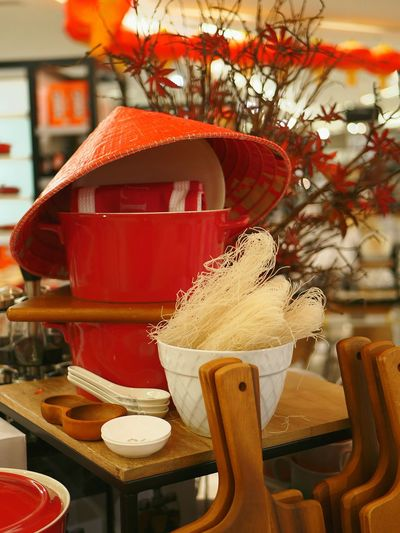 Food and crockery with asian style conical hat on restaurant table