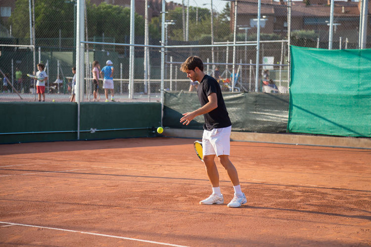 Professional tennis player playing tennis on a clay tennis court on a sunny day. Match Afternoon Court Kick Lifestyle Recreation  Set Sunny Action Clay Competition Competitive Sport Game Healthy Leisure Activity person Play Player Playing Practicing Professional Racket Serve Serving Tennis 🎾