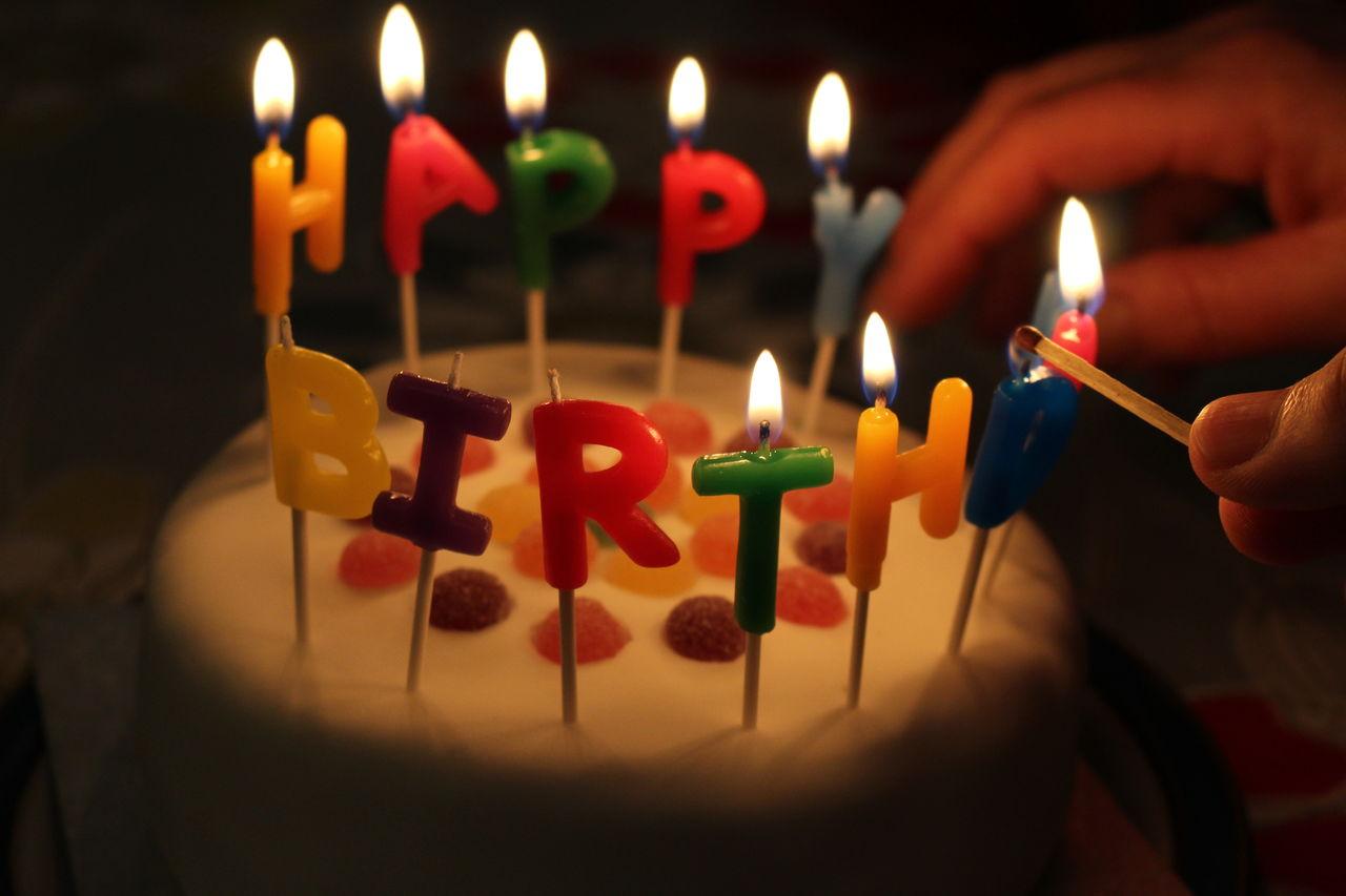 Hand Lighting Candles On Birthday Cake