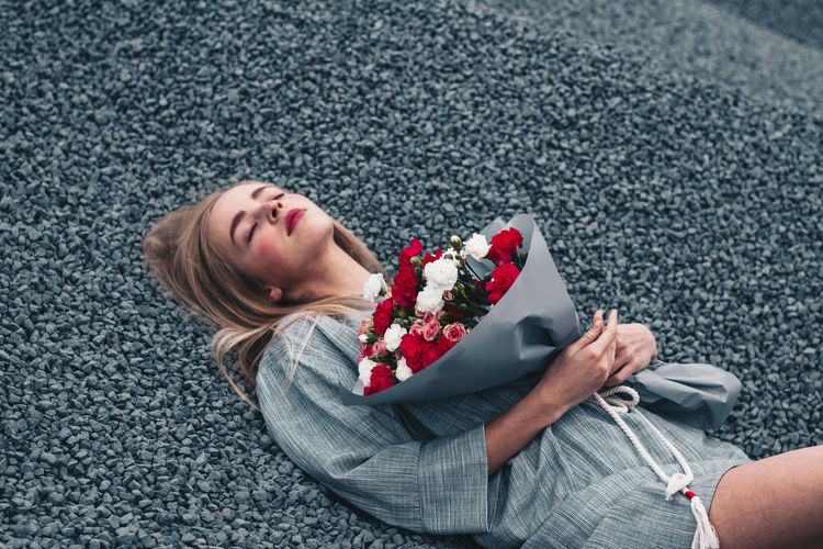 High angle view of woman with bouquet lying on gravels