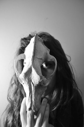 Close-up portrait of woman holding animal skull on face against wall