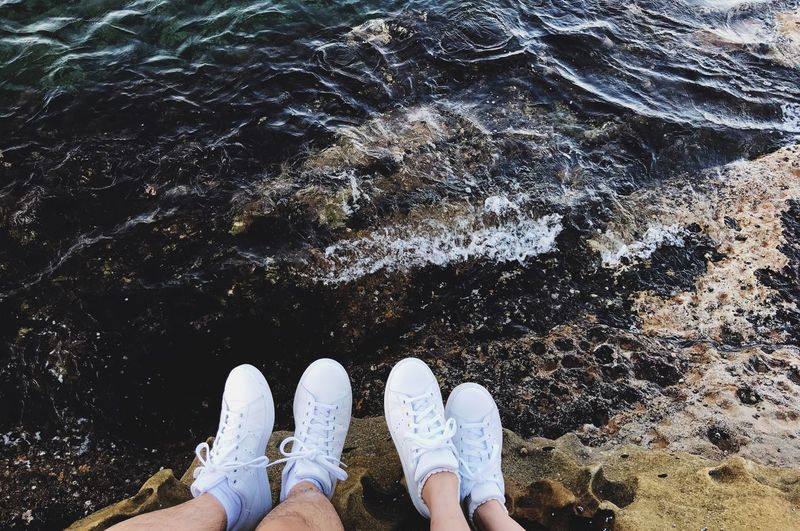 Low Section Of Friends Sitting On Rock At Beach
