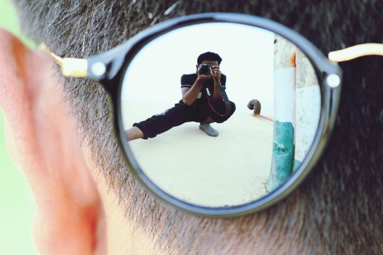 Reflection of man in sunglass photographing through digital camera