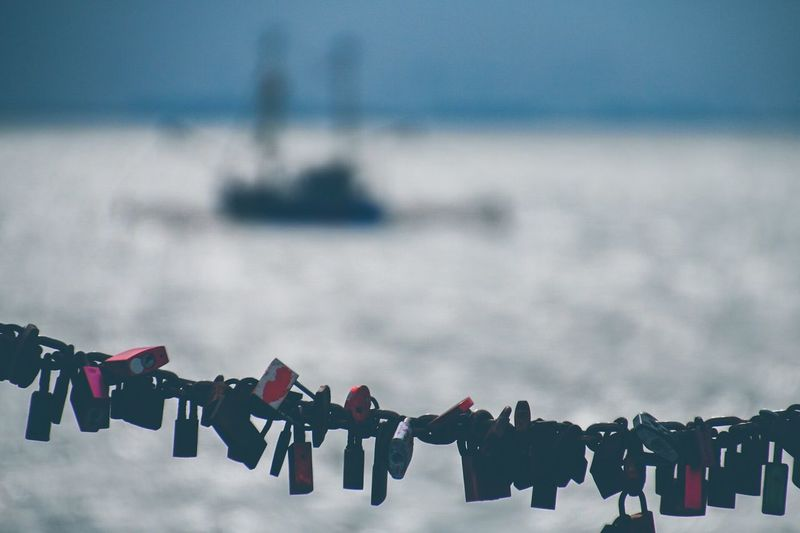 Close-Up Of Love Locks With Sea In Background