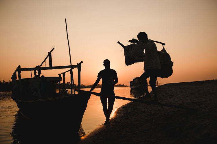 Daily chores of a village in Assam ... Travel Light And Shadow Exploring Body Part Silhouette Cultures Chores Boat Tinsukia Assam Brahmaputra Carrying Men Working Hardwork Labour Storytelling Water Full Length Sunset Occupation Fisherman Standing Teamwork Men Silhouette Worker The Photojournalist - 2019 EyeEm Awards The Traveler - 2019 EyeEm Awards