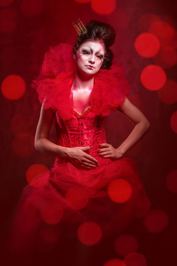 Portrait of young woman wearing red costume against defocused background