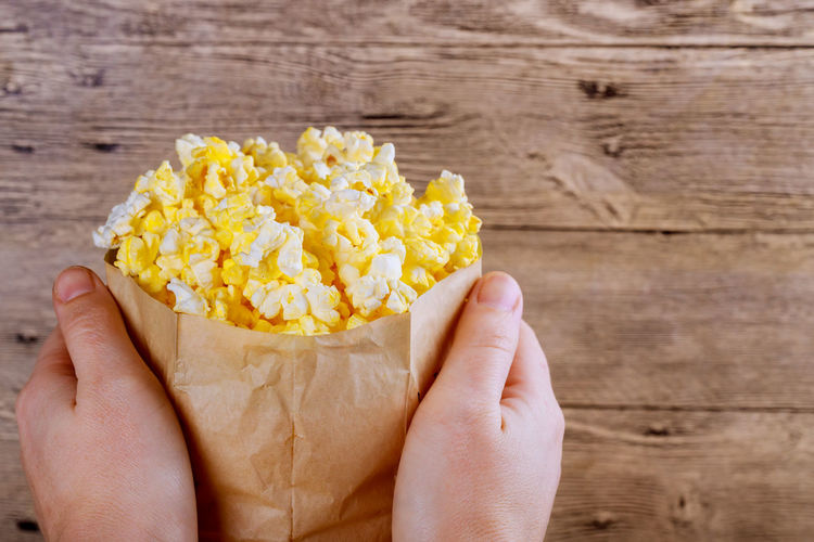 Cropped hands holding popcorns in paper bag on wooden table