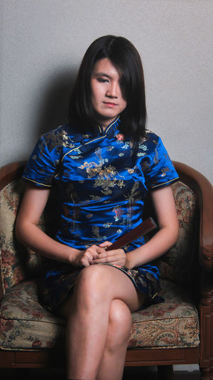 Female model wearing traditional clothing while sitting on chair against wall