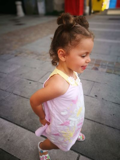 Side View Of Cute Girl Standing On Footpath