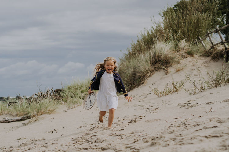 Child girl in jacket laughing and running with clock at the beach