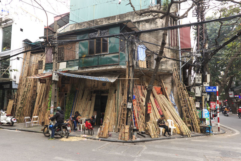 Hanoi, Vietnam - February 22, 2016: People selling Bamboo tools in the old town on Hanoi Alley Architecture Building Building Exterior Built Structure Cable City City Life City Street Day Hanoi Hanoi Vietnam  Ho Chi Minh Mausoleum Old Town One Pillar Pagoda Outdoors Power Line  Residential Building Residential Structure Road Sky The Way Forward Tourists Town Vietnam