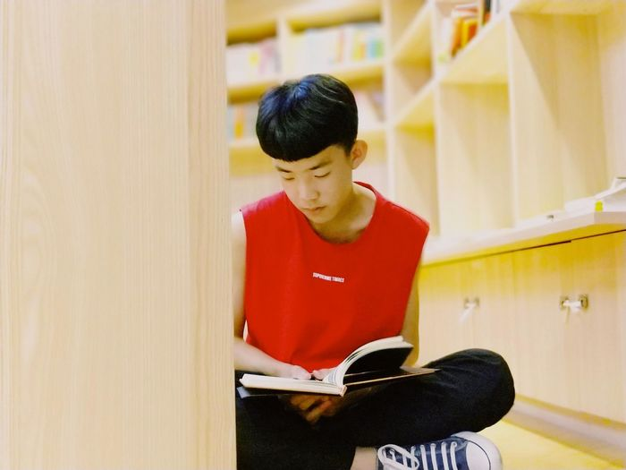 Teenage Boy Reading Book While Sitting At Home
