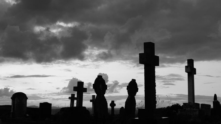 Crosses And Tombstones Against Cloudy Sky In Cemetery At Dusk