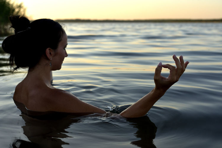 Shirtless woman meditating in sea during sunset