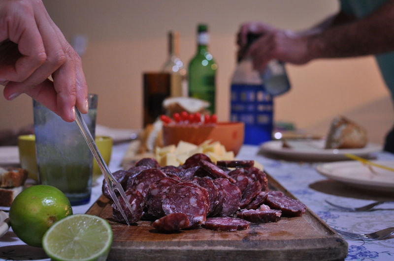 La picada Argentina. Gancia Soda Close-up Cutting Focus On Foreground Food Food And Drink Freshness Fruit Healthy Eating Holding Human Body Part Human Hand Indoors  Lifestyles Meat Men Picada Argentina Plate Preparation  Ready-to-eat Real People SLICE Table Wine