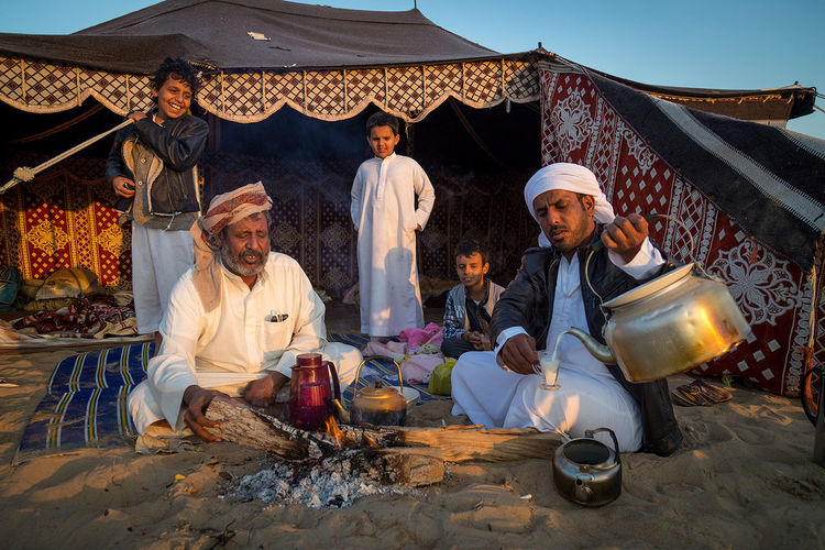 Bedouin Family enjoying their morning coffee during the Al Dhafra Camel festival in Abu Dhabi Abu Dhabi Adult Bedouin Bedouin Tribes Day Mature Adult Mature Men Men Outdoors People Real People Sitting Sky Tent The Portraitist - 2017 EyeEm Awards