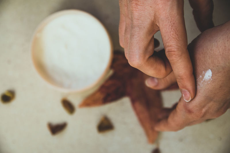 Close-up of hands applying lotion