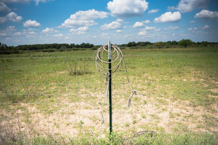 Metal fence on field against sky
