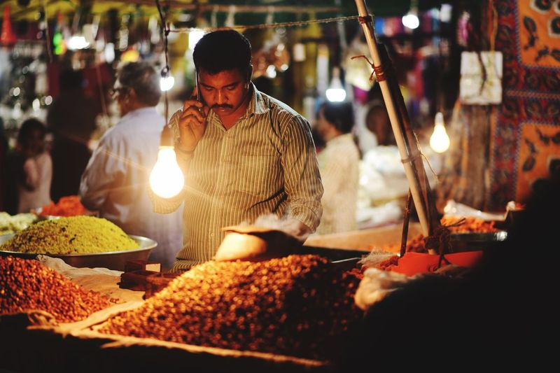 Market vendor answering phone while working at illuminated market stall