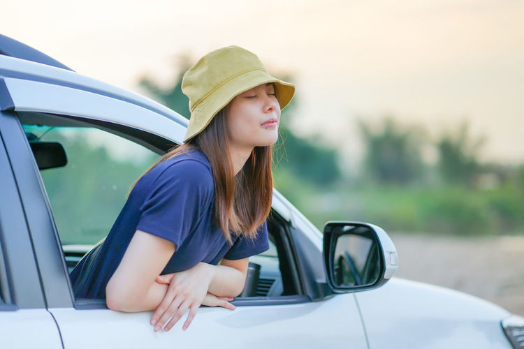 Woman wearing hat while sitting in car