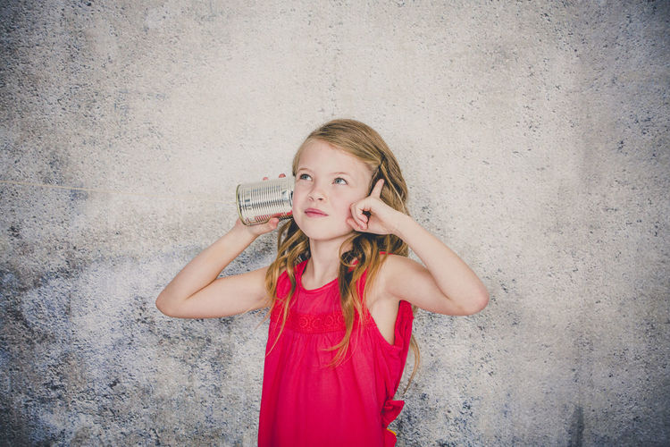 Cute girl playing with tin can phone while standing against wall
