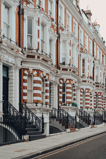 Row of traditional victorian houses with stoops in kensington and chelsea, london, uk.