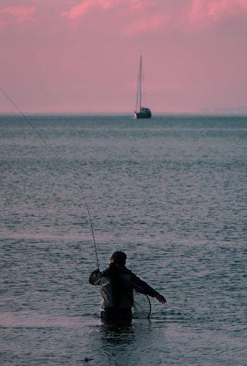 Man Fishing In Sea Against Sky