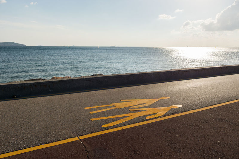 Yellow markings on promenade by sea against sky