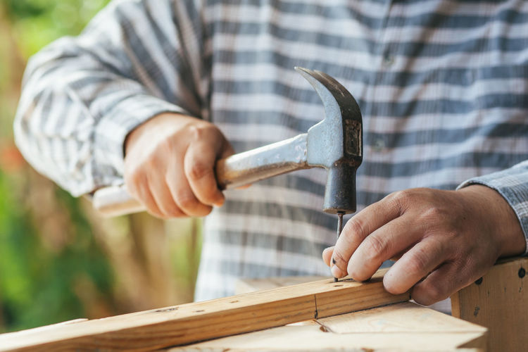 Midsection of man hammering nail in wood at workshop