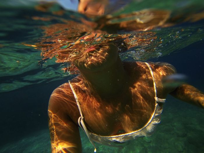Close-Up Of Woman Swimming Undersea