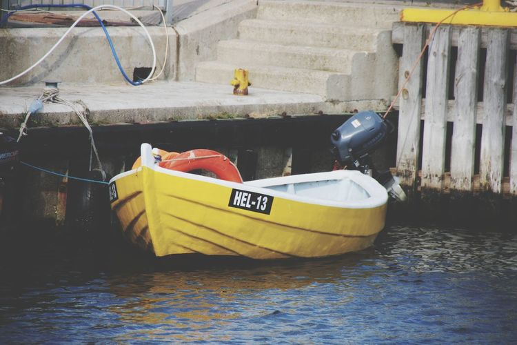 View of yellow boat moored at river