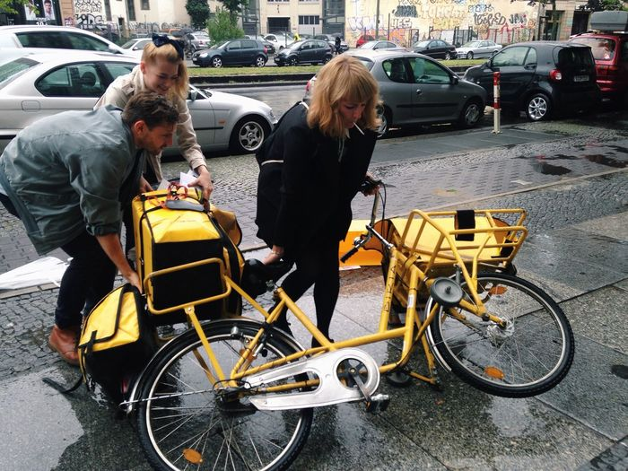Man and woman helping mid adult lifting bicycle on sidewalk