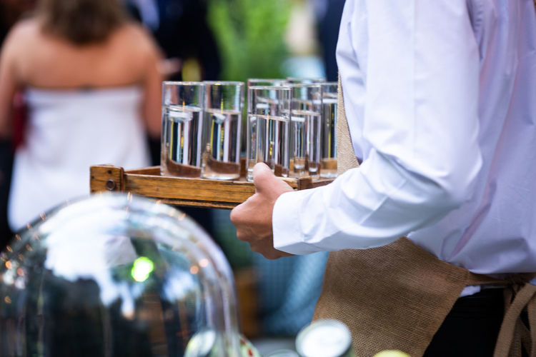 Midsection of waiter holding tray with drink glasses