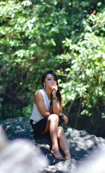 Young woman sitting on rock in forest