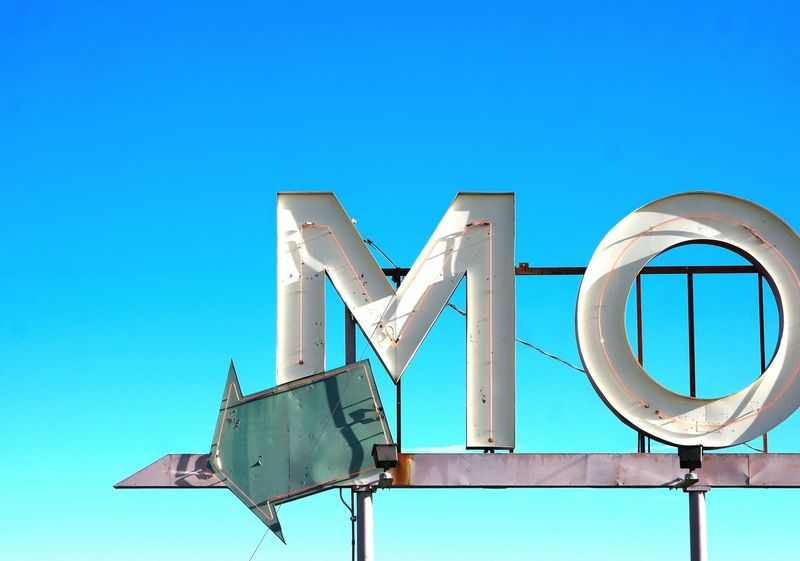 Blue Clear Sky Low Angle View No People Business Finance And Industry Service Accomodations Motel Accomodation Information Medium Pointing Arrow Arrow Symbol Sign Motel Sign Motels Industry Sleep Sleepy Symbol Signage Text Business M O