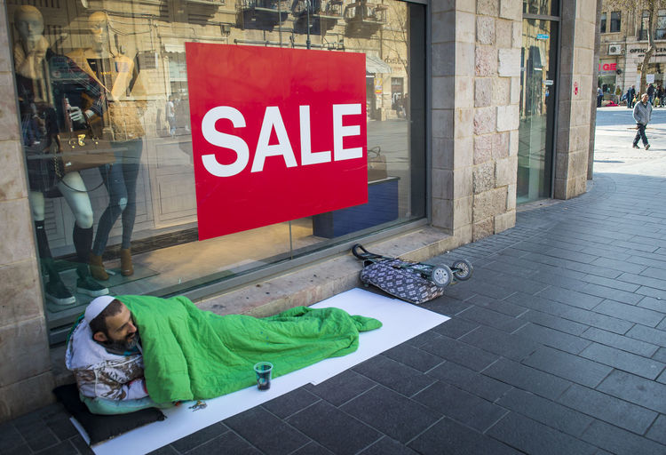 A beggar man lies at the supermarket showcase Adult Adults Only Beggar Day Doss House Full Length Indoors  Jerusalem Jew One Person Only Men People Poverty Poverty Lives. Shop-window