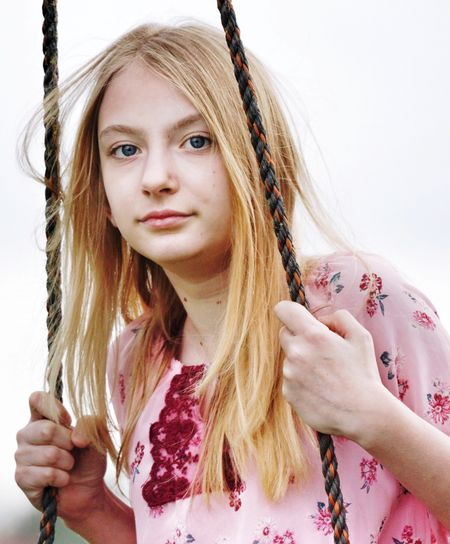 Close-up portrait of girl on swing