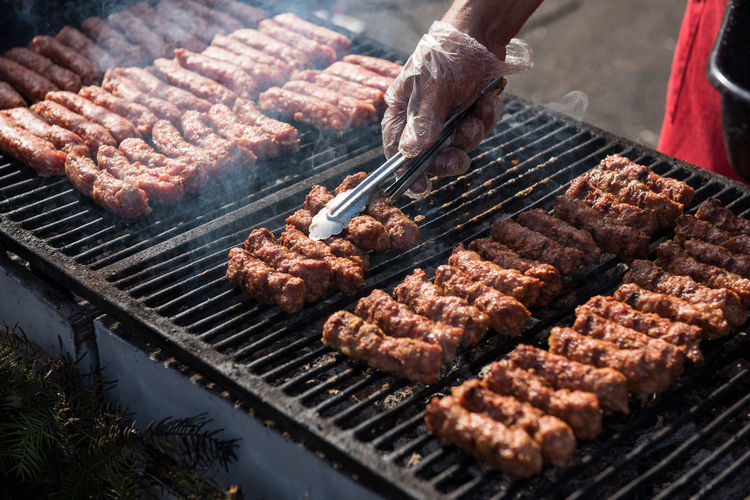 Cropped hand of man preparing meat on barbecue grill