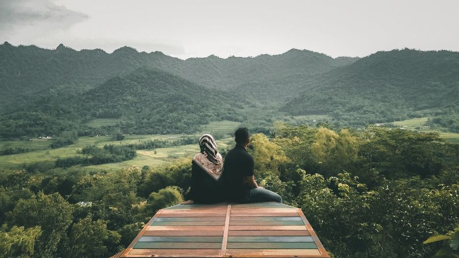 Couple Sitting At Observation Point Against Sky
