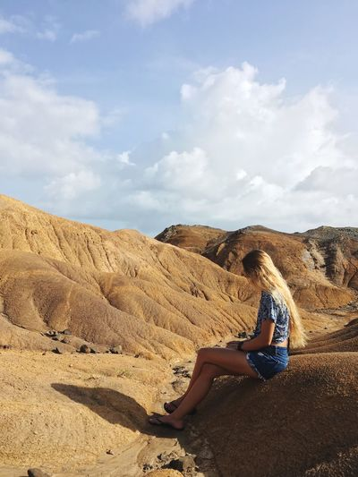Woman sitting on rock in desert against sky