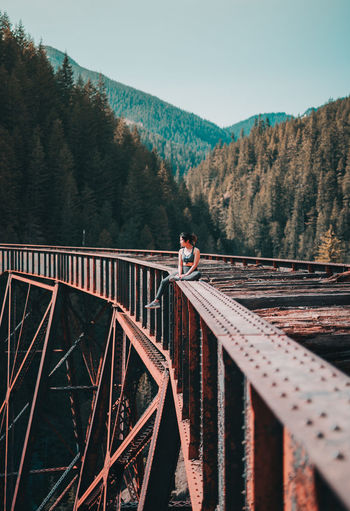 Woman sitting on damaged bridge against sky