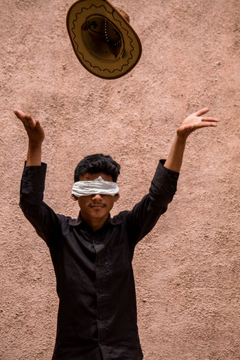 Blindfolded Boy Throwing Hat While Standing Against Wall