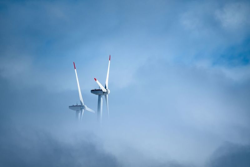 Low angle view of windmill against cloudy sky