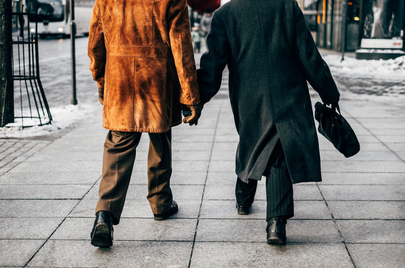the elderly couple walks in hand down the street Adult Adults Only Celebration City City Life Cold Temperature Couple Day Human Body Part Low Section Outdoors People Street Togetherness Two People Walking Winter The Street Photographer - 2017 EyeEm Awards