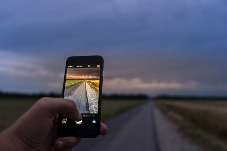 Cropped image of hands photographing country road