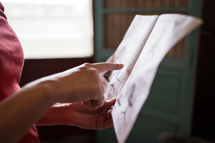 Midsection of woman holding paper at home