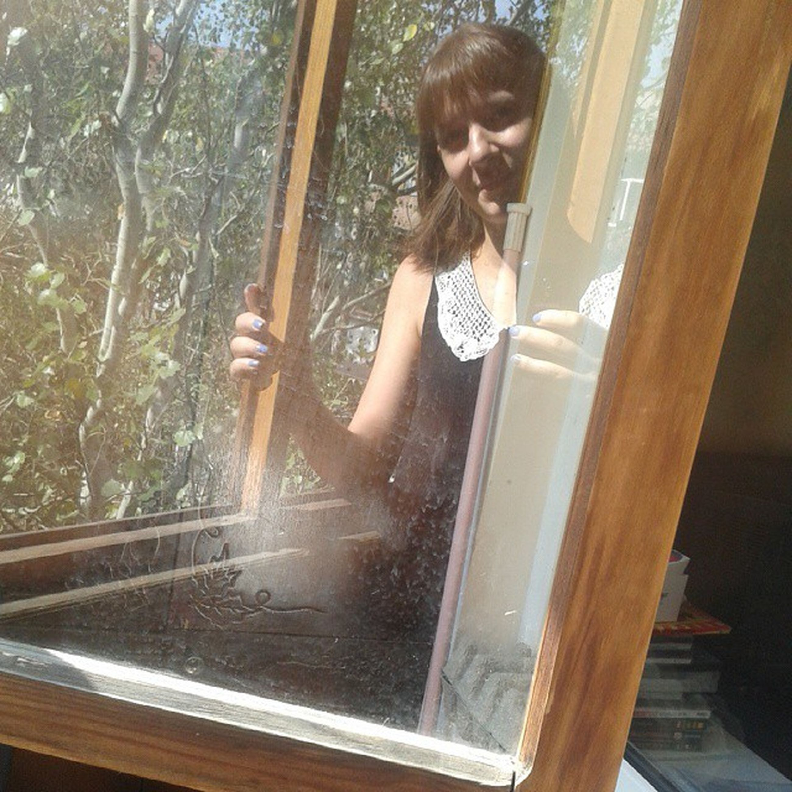 indoors, lifestyles, window, young adult, person, glass - material, full length, leisure activity, transparent, young women, casual clothing, standing, looking through window, reflection, side view, three quarter length, sitting, built structure