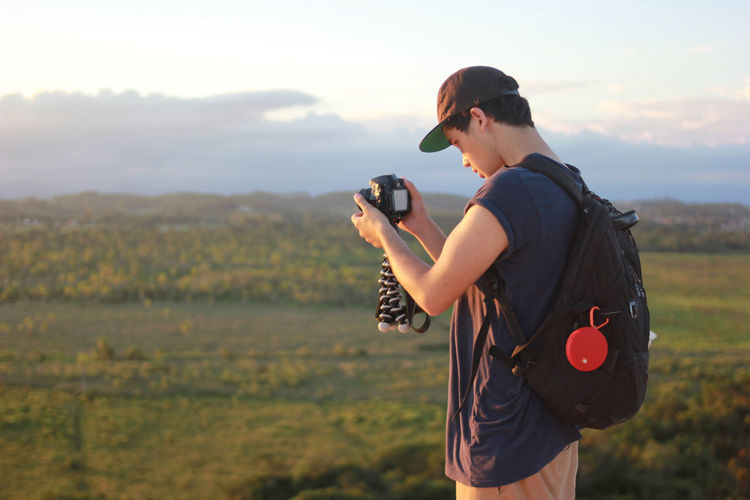 Man photographing on landscape against sky